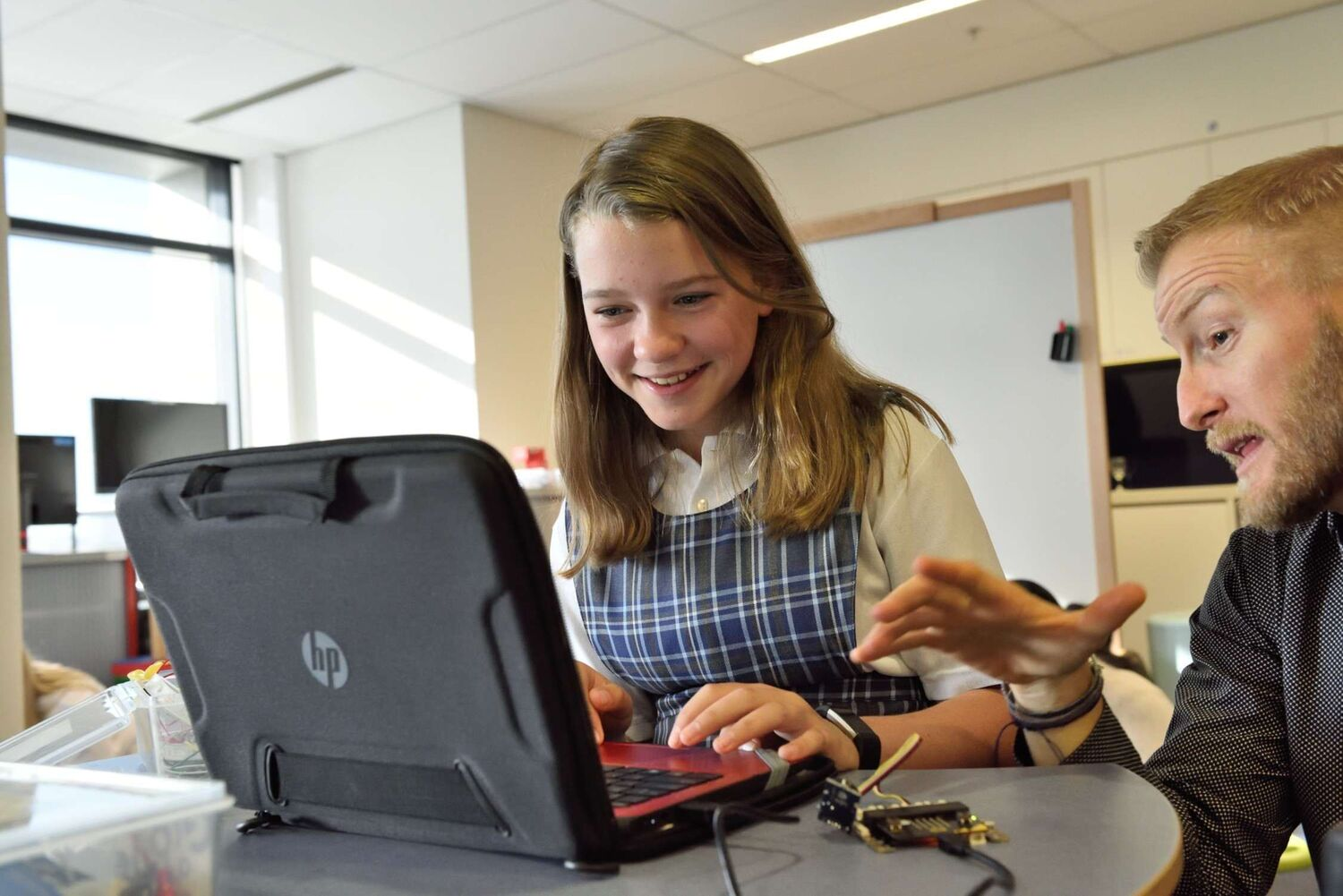 teenage girl at computer with mentor