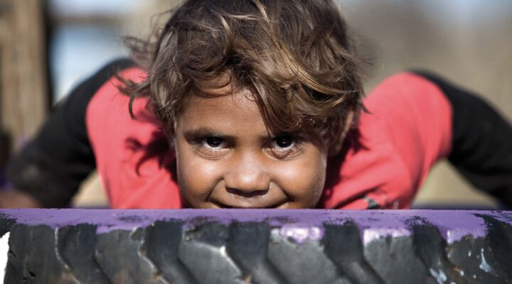 Aboriginal Child On A Tyre Looking Into Camera