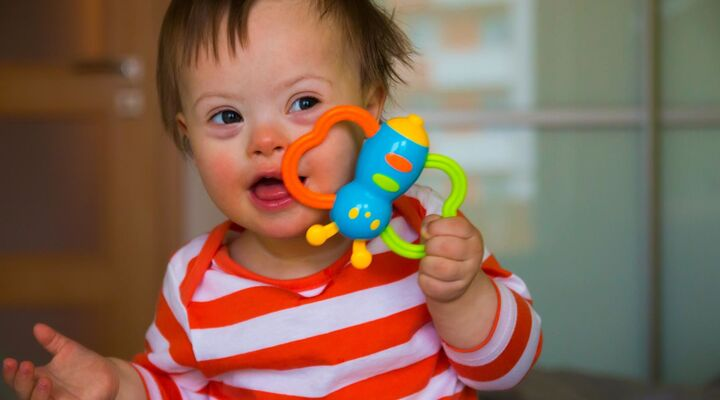Cute Baby Boy With Down Syndrome Holding Coloured Butterfly Toy