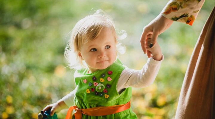 Girl In Green Dress With Love Heart Buttons Holding Mothers Hand And Toy In Other Hand