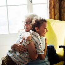 Grandmother Sitting In Green Armchair Hugging Grandson In Striped Polo Top