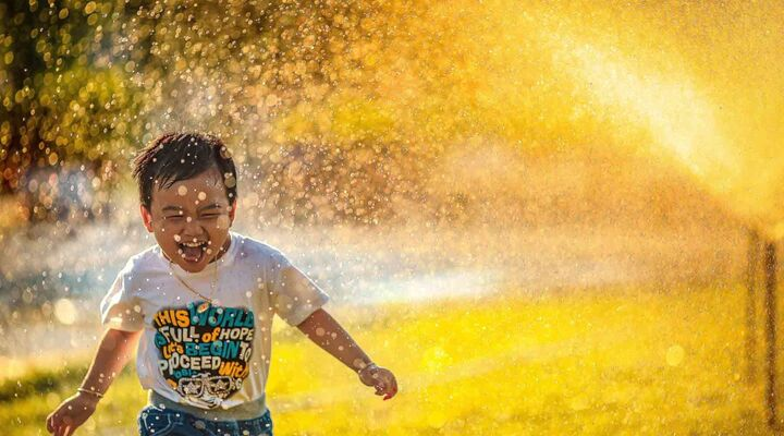 Asian Boy Running Through Sprinklers Which Are Reflecting Bright Golden Light
