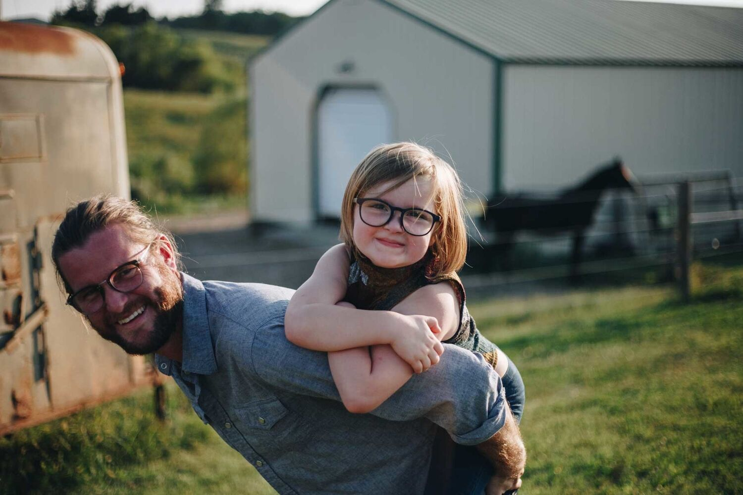 Father With Beard And Long Hair Giving Daughter Piggy Back On Farm