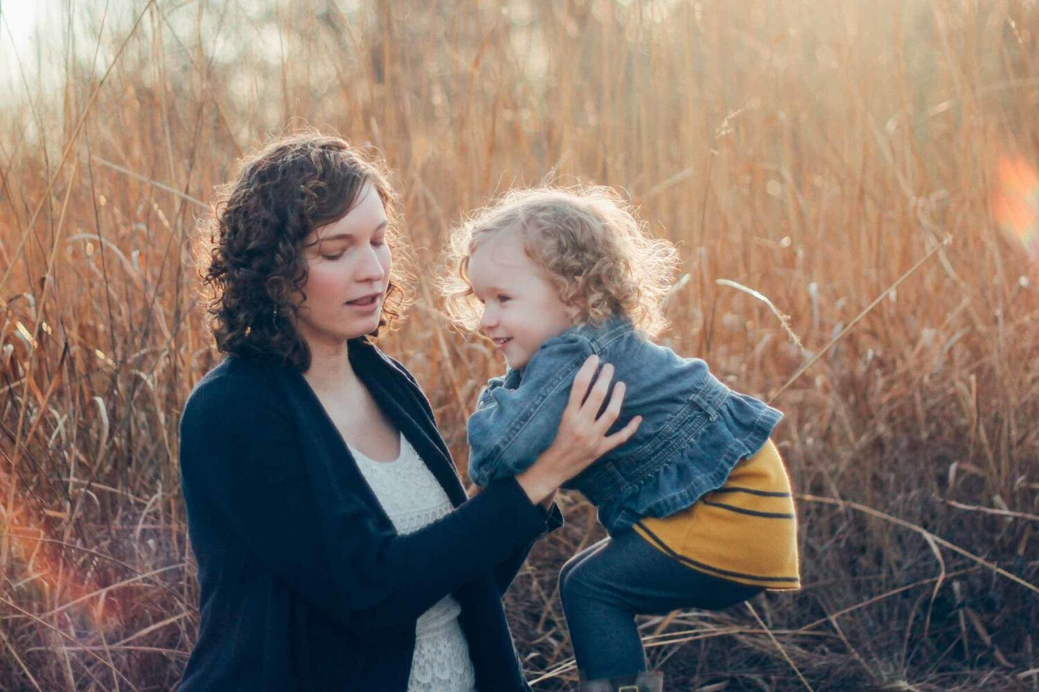 Mother Holding Young Child In Field Of Tall Dead Grass