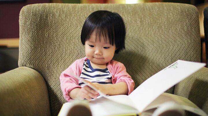 Small Asian Girl Reading A Book In A Beige Armchair