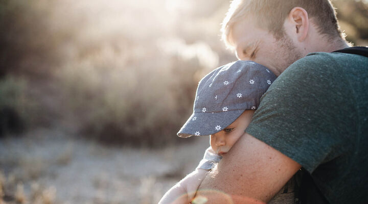 Father Hugging Young Child With A Hat On