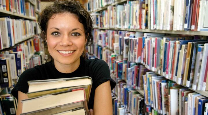 Young Woman Carrying Stack Of Books Standing In Library Rows