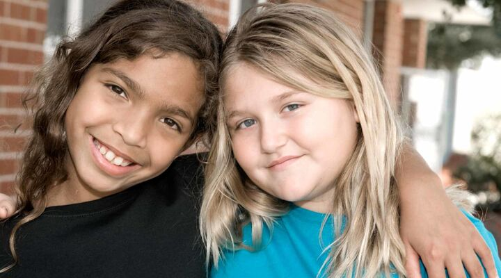 Aboriginal Girl Smiling With Arm Around Friend With Blonde Hair