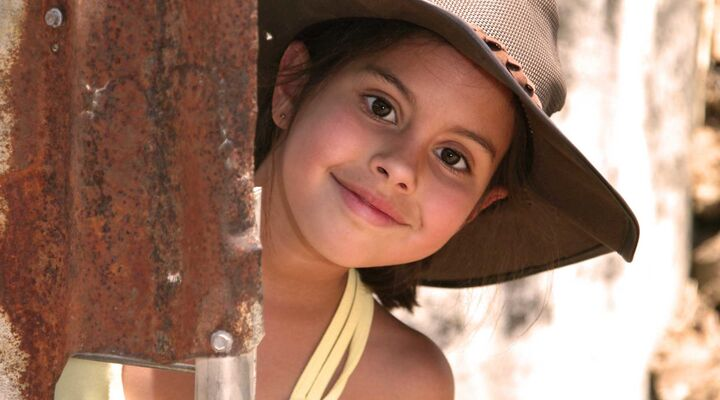 Girl With Dark Eyes And Wide Brimmed Hat Leaning Out Of Rusty Corrugated Iron Wall