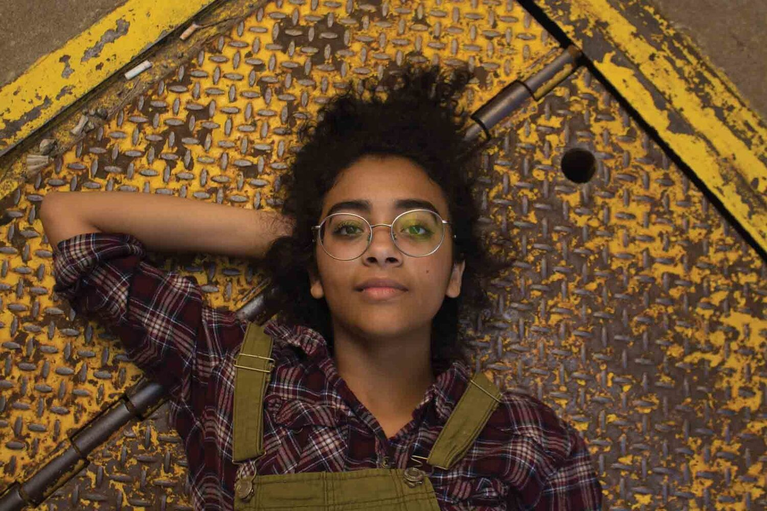 Young Woman With Big Glasses Lying On Metal Floor