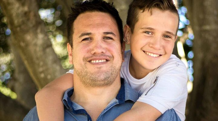 Boy With Arms Around Dads Neck Both Smiling Into Camera