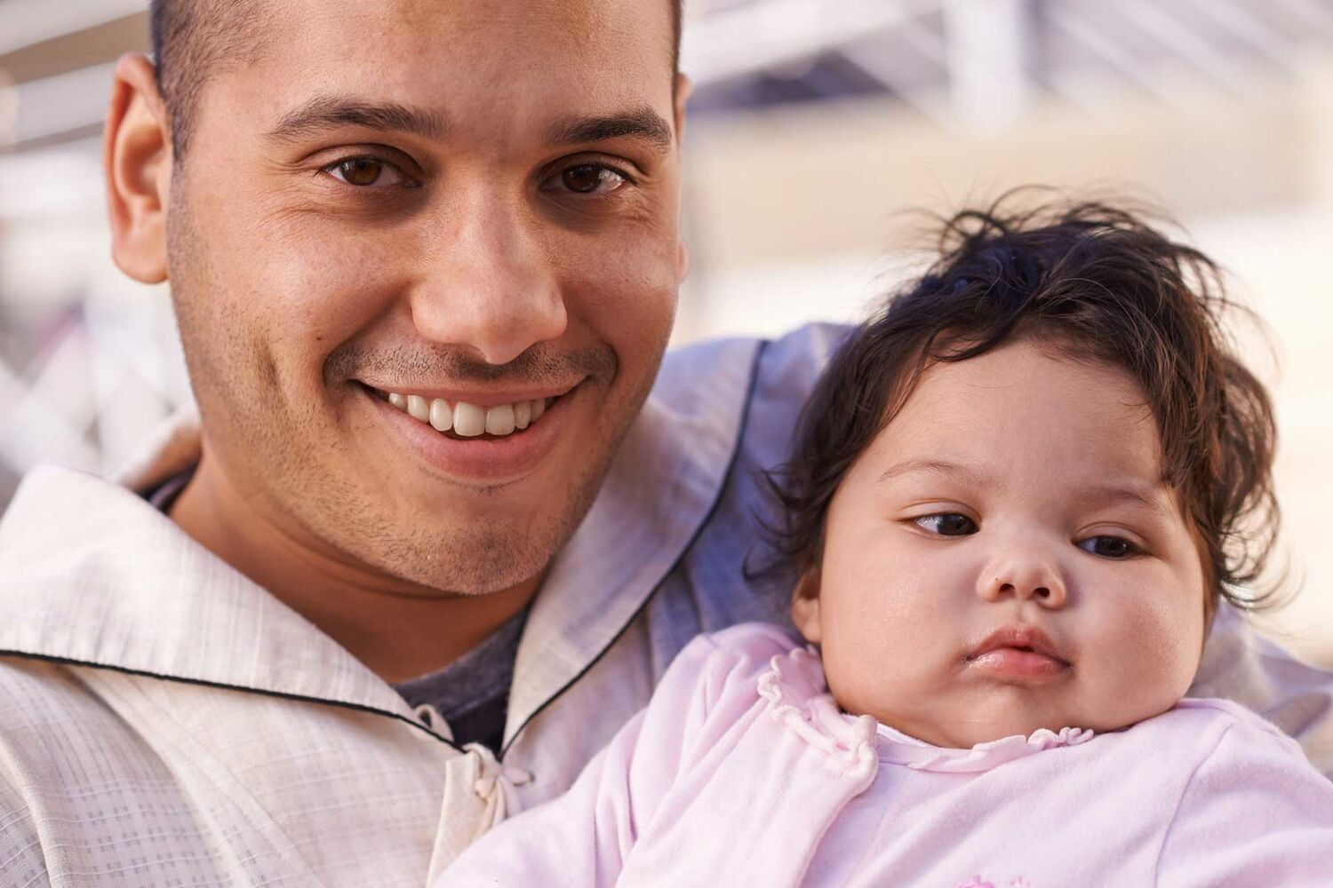 Father Holding Baby Girl With Chubby Cheeks Smiling Into Camera
