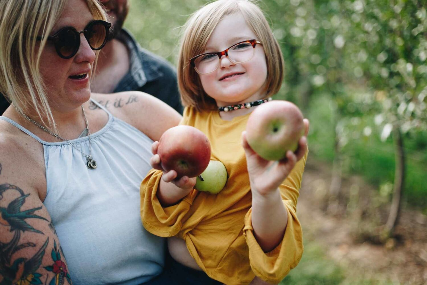 Girl Holding Apples Being Held By Mother In Orchard