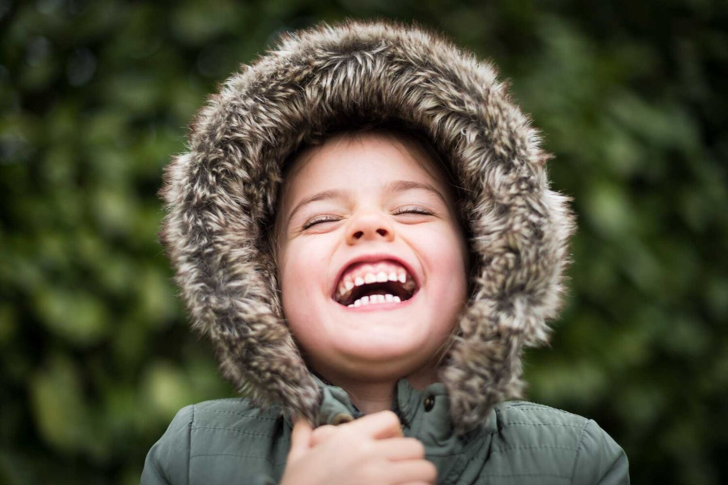 Child Wearing Jacket With Furry Hood Laughing With Eyes Closed