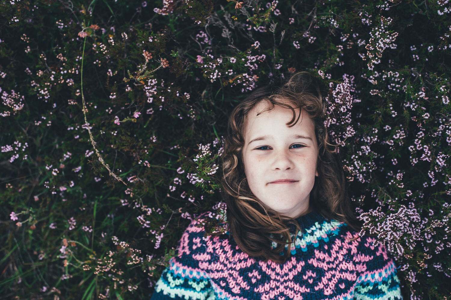 Girl in colourful woollen jumper leaning against hedge with flowers