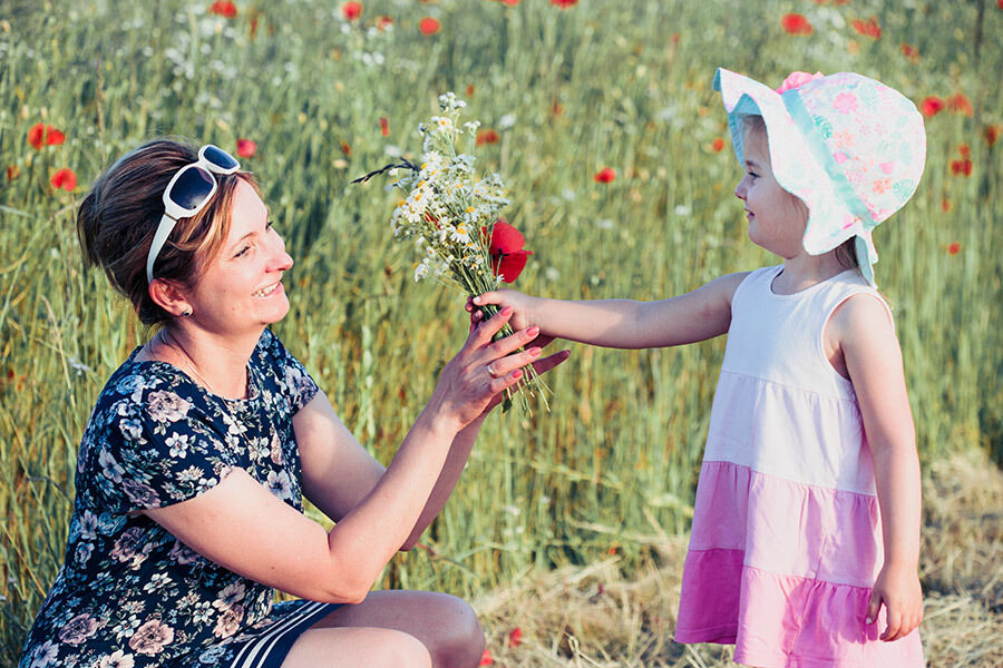 Mother And Her Little Daughter In The Field Of Wild Flowers Little Girl Picking The Spring Flowers