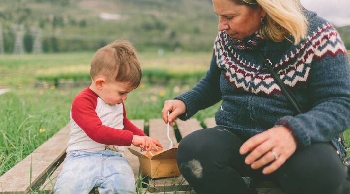 Grandmother And Toddler Sitting On Wooden Crate In Field Eating Take Away