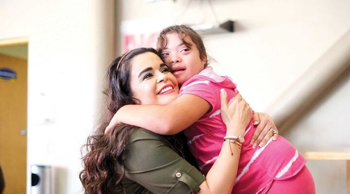 Girl With Down Syndrome In Pink Hugging Woman With Long Hair