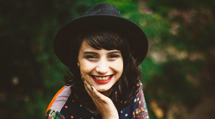 Young Woman With Red Lipstick Wearing Black Felt Hat Smiling At Camera With Greenery Behind Her