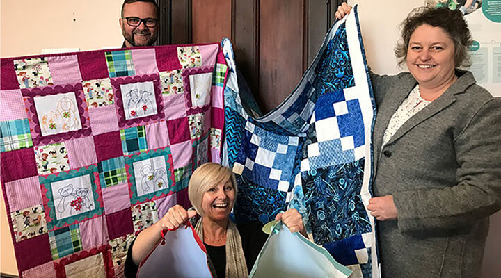 MacKillop's NSW team members holding quilts