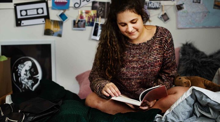 Teenage Girl In Knitted Jumper Reading Book On Her Bed With Pictures On Wall