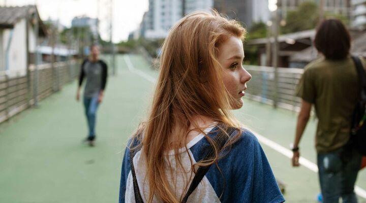 Young Woman With Long Red Hair And Backpack Looking Over Shoulder