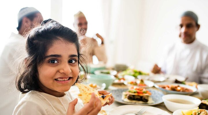 Young Islamic Girl Smiling Holding Pita Bread With Family In Background At Dining Table