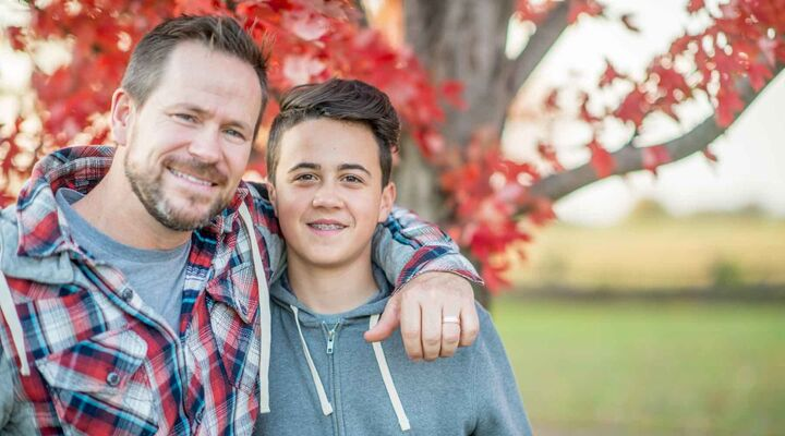 Dad Standing With Arm Around Son With Autumnal Tree In Background