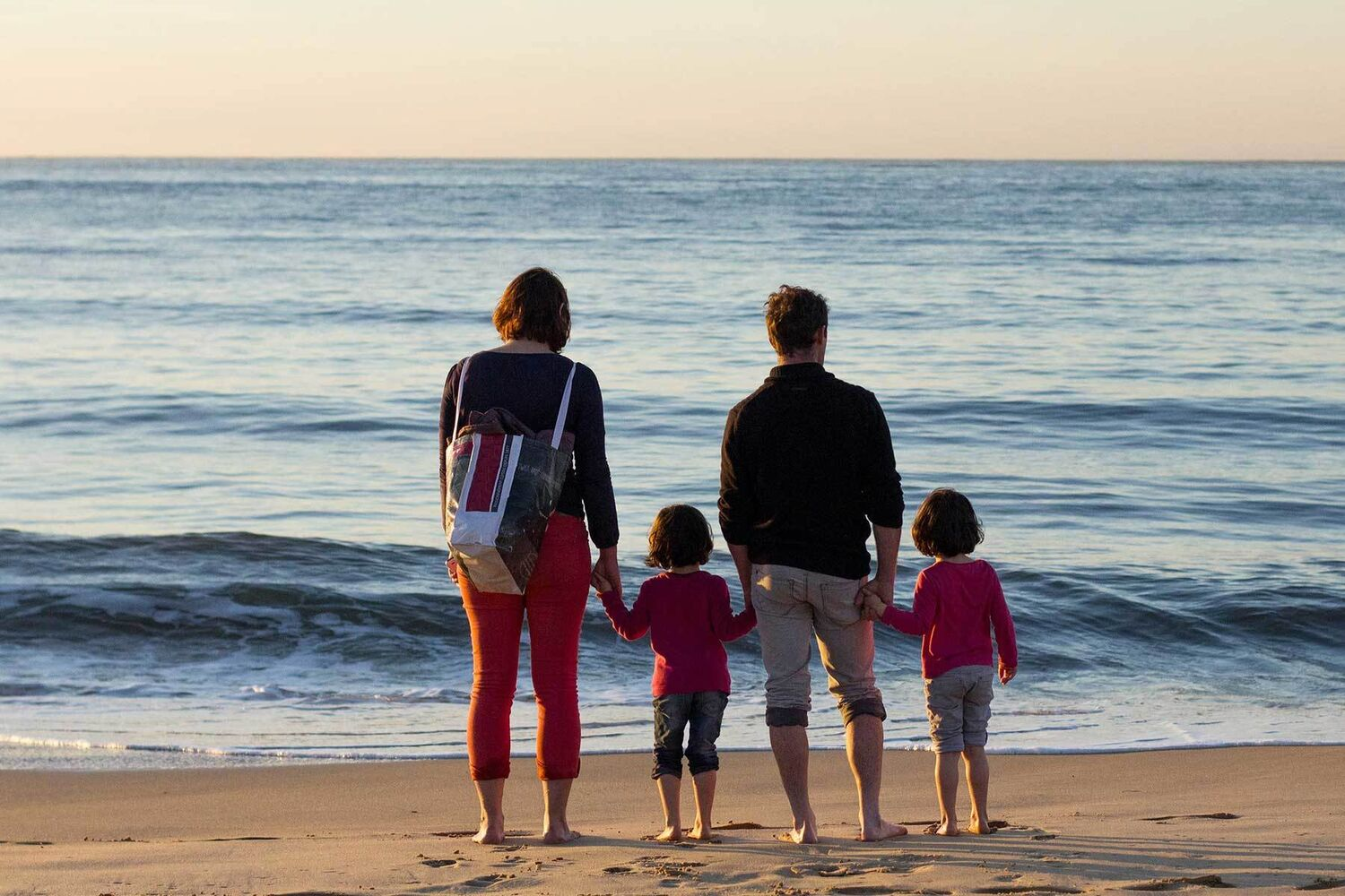 Family Standing On Beach Facing Away From Camera