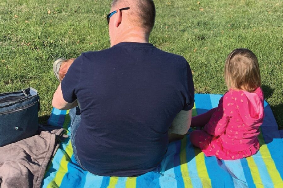 Dad Sitting With Baby In Arms And Child On A Picnic Rug