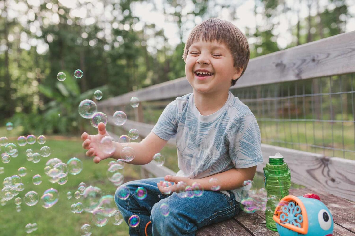 Boy Wearing Jeans And Tshirt Sitting On Bench Outside Playing With Bubbles