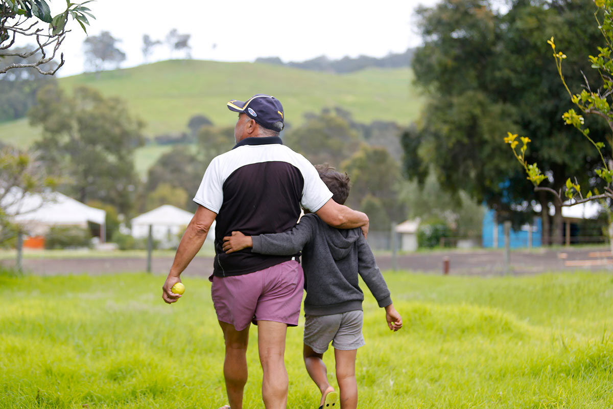 Foster Carer Francis Khan Walking With Arm Around Young Boy Outdoors At Roelands Village