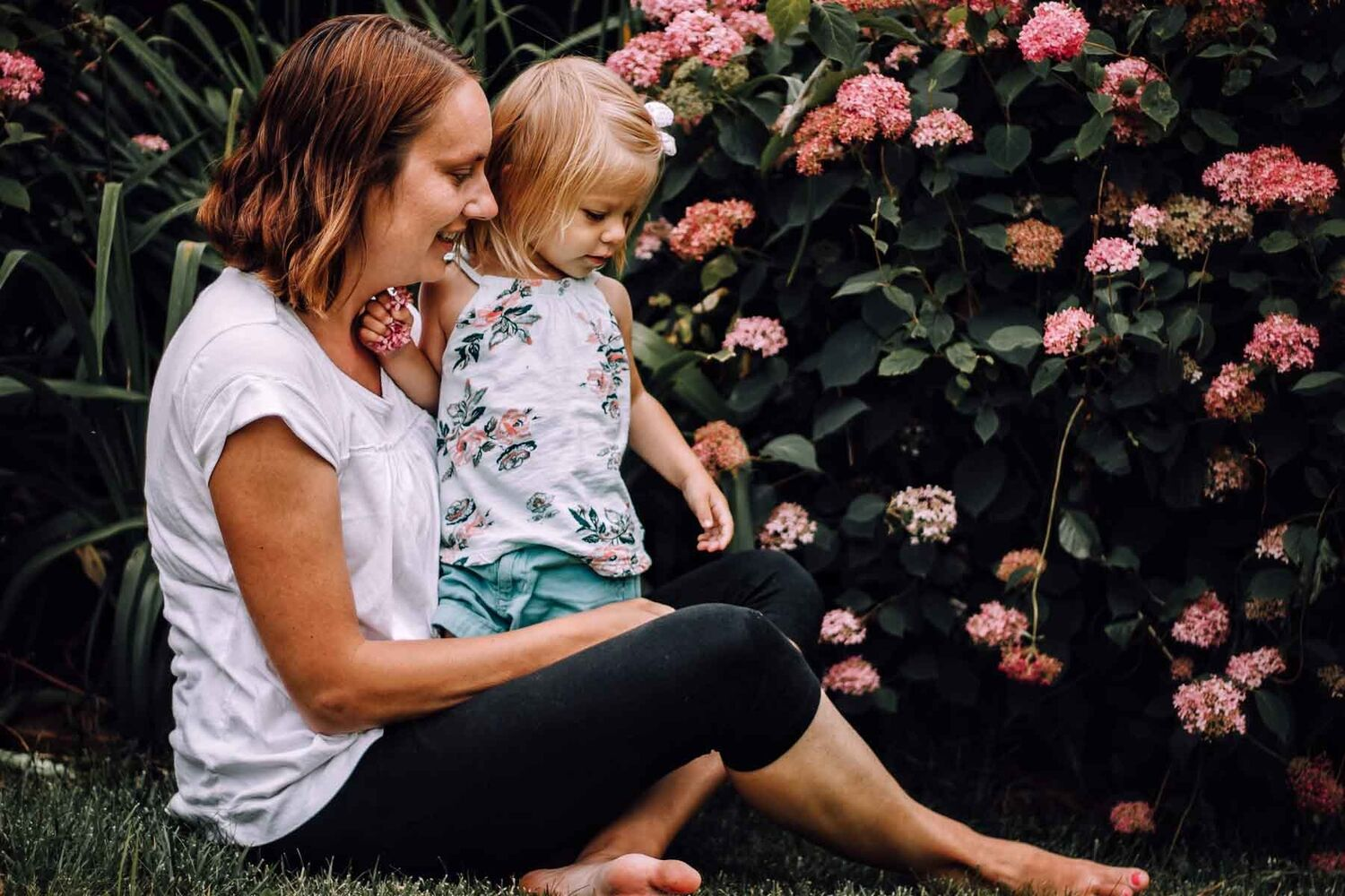 Mother Sitting On Grass With Daughter Standing In Lap In Garden