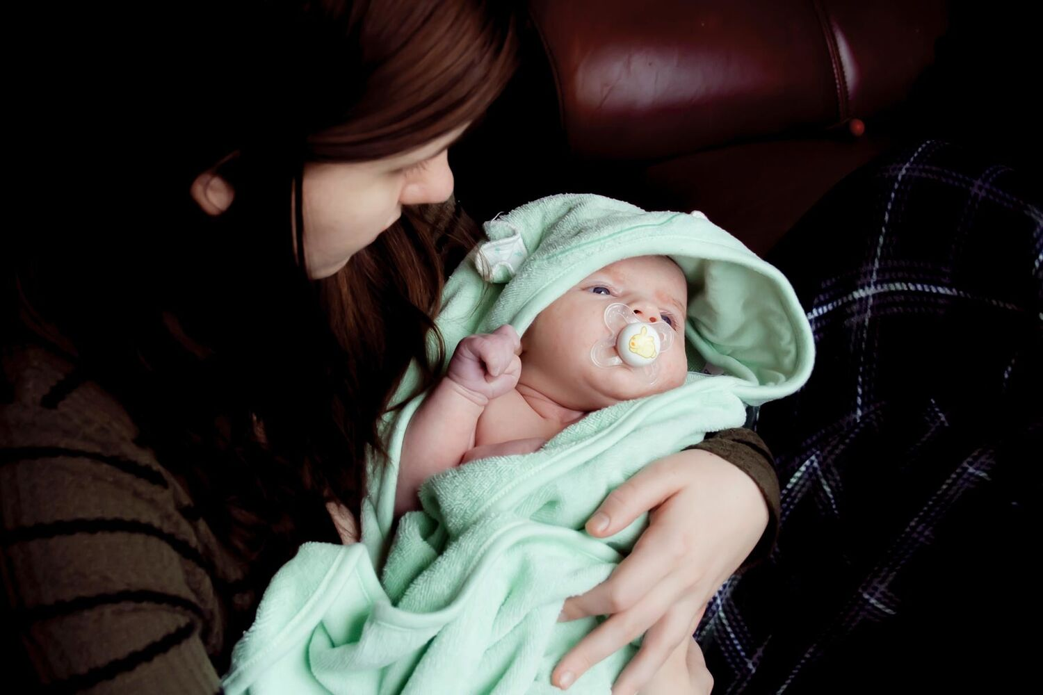 Young Mother Holding Baby In Green Swaddle With Dummy