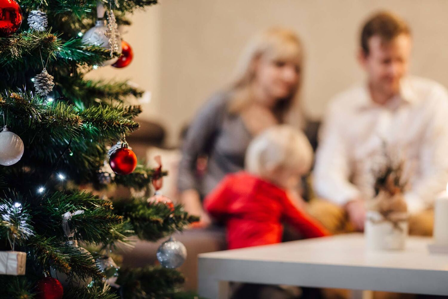 Decorated Christmas Tree In Focus With Mother Father And Young Son In Background