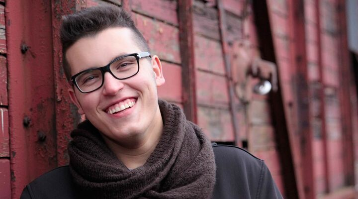 Young Man Wearing Glasses And Scarf Standing In Front Of Red Wall Smiling