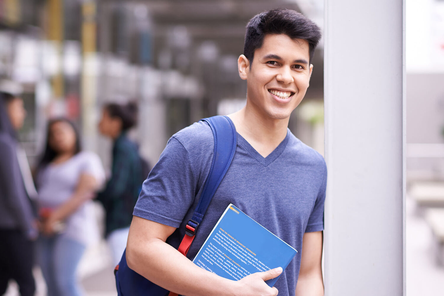 Young Man With Dark Hair In Blue Tshirt Wearing Backpack And Holding Textbook